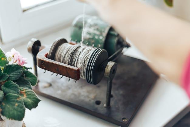 糸のボールを作るための機械の助けを借りてボールを作る老婦人の手