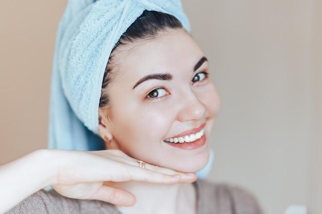 美容トリートメント後のヘアタオルを着てスパスキンケア美容女性。