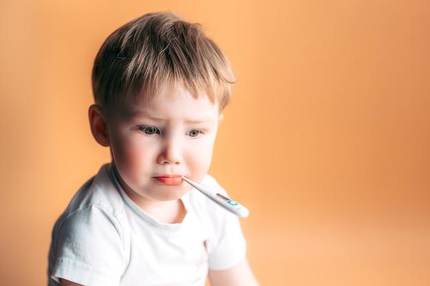 オレンジ色の背景に悲しい顔をして彼の口に温度計を持つ病気の子供