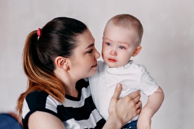 Плачущая девочка-малышка утешается своей матерью