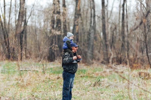 幸せな週末のコンセプトです。幸せな祖父と孫が森を歩いています。