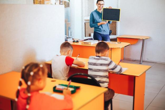 先生は教室で子供たちに教えます