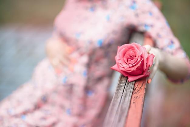 妊娠中の女性が待っているピンクのバラの女の子を押しながらバンプに触れる