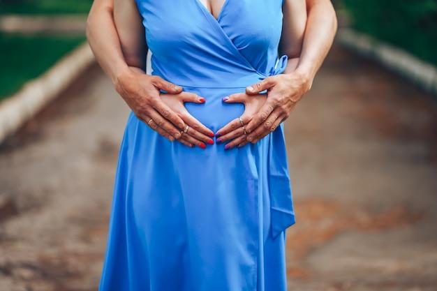 妊娠中の女性と彼女の夫は心臓の形でおなかに手を取り合って