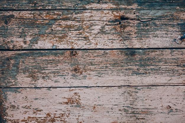 ピンクのペンキと古い汚れた木製の背景