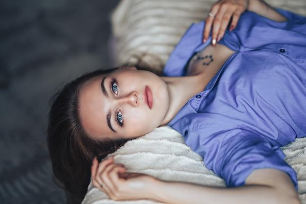 Сексуальная молодая красивая женщина с голубыми большими глазами светлыми волосами, лежа на кровати у себя дома в синей рубашке