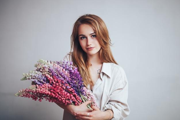 Сексуальная молодая красивая женщина с голубыми большими глазами, светлыми волосами, лежа на кровати у себя дома в серой рубашке с люпином в руках