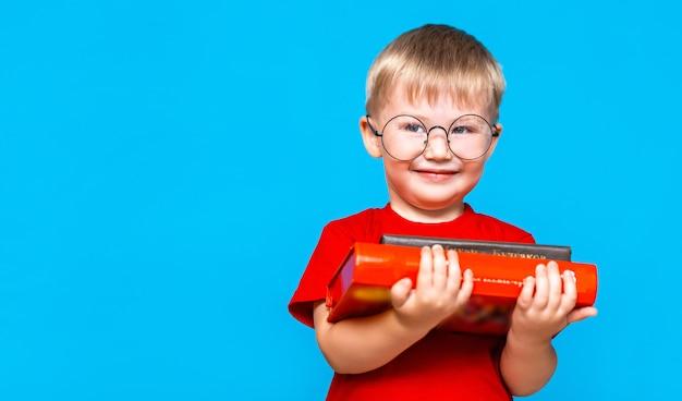 書籍のスタックを保持している丸眼鏡の少年の笑顔。教育。学校へ行く準備ができて