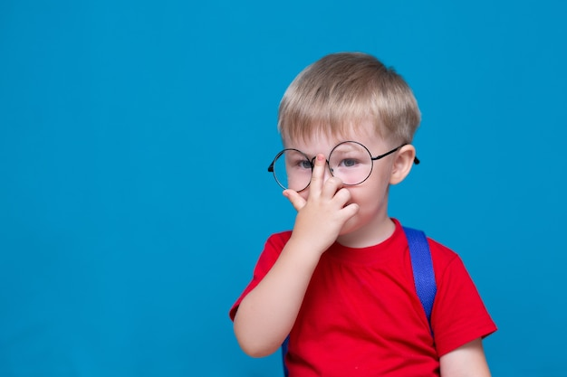 Счастливый улыбающийся мальчик в красной футболке в круглых очках впервые идет в школу. ребенок со школьной сумкой. малыш снова в школу