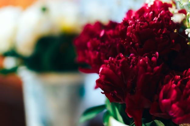 テーブルの上に立って、女性へのギフトの花瓶に非常に美しいパイオンズ