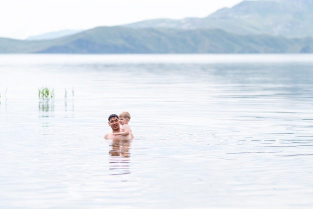 海で泳いでいる幼い息子を持つ父、