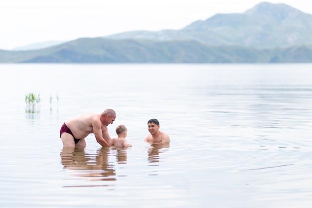 彼の祖父と父と子供の遊びと海で泳ぐ