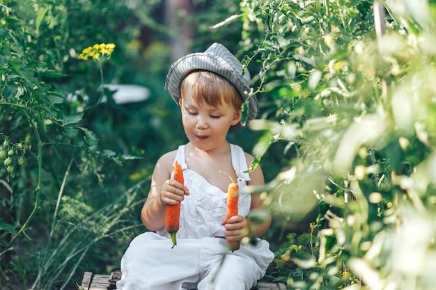 ニンジンと緑の草に座っているカジュアルな服装の赤ちゃん農家