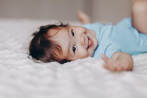 Милая смеющаяся годовалая девочка лежит на кровати