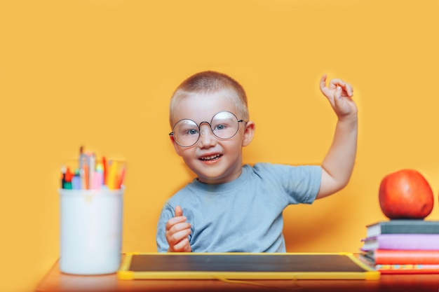 絵を描いて、アイデアを持っている彼の机で宿題をしている少年