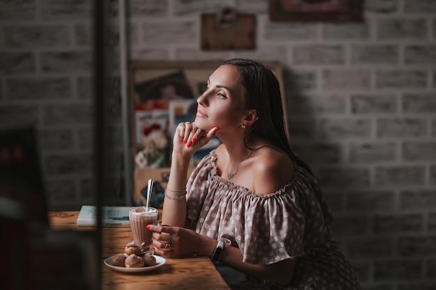Молодая женщина, сидя в кафе, держа ложку и стакан с кофе или молочный коктейль со взбитыми сливками, глядя на окна