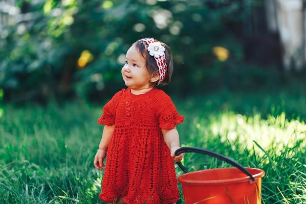 美しい咲く果樹園でピクニックを楽しんでいる赤いドレスを着てニット花の冠を持つ愛らしい幸せな幼児の女の子