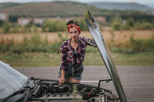 灰色の短いデニムのショートパンツの少女の背面図は、車を修理しています。ボンネットが開いている黒い車の近くのショートパンツ。ロードトリップでの車の問題。エンジンを修理するブルネット