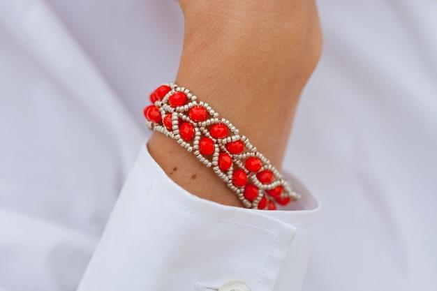 女性の手にスタイリッシュな赤いビーズのブレスレット