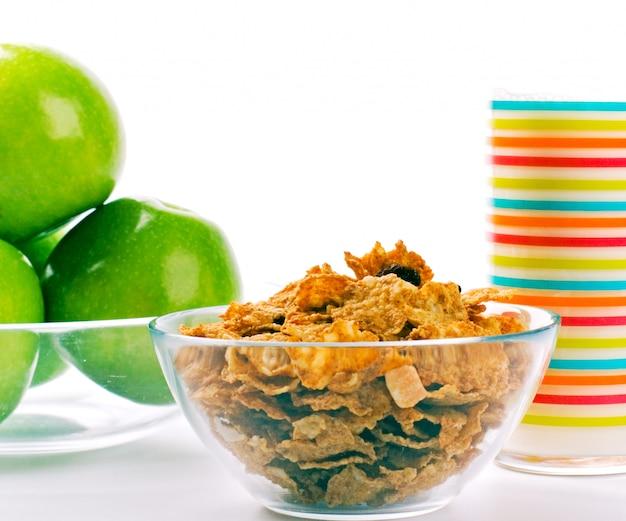 健康的な朝食:コーンフレーク、牛乳と青リンゴのガラス