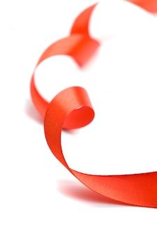 Красная атласная лента крупным планом на белом фоне