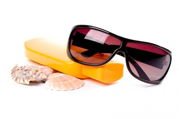 Солнцезащитные очки, ракушки и лосьон крупным планом на белом фоне