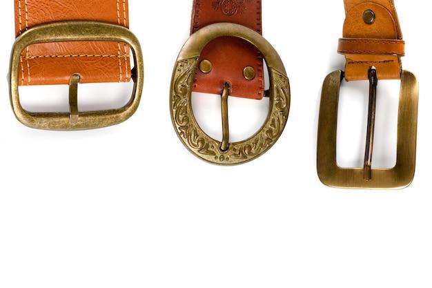 Три коричневых кожаных ремня с бронзовыми пряжками на белом фоне