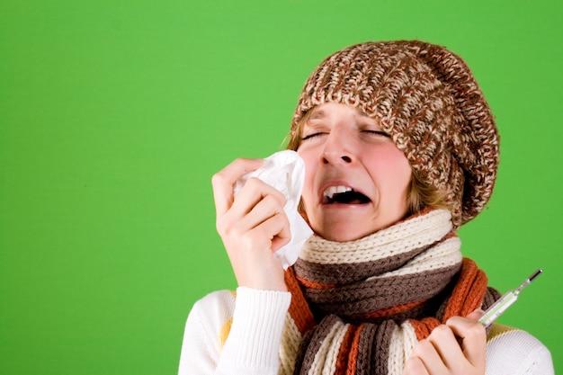 Портрет холодной девушки чихает с платком и термометром на зеленом фоне
