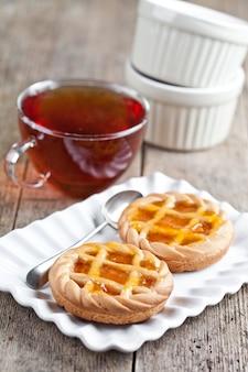 白いセラミックプレートと素朴な木製のテーブルの上の紅茶のカップを充填マーマレードまたはアプリコットジャムの焼きたてのタルト。