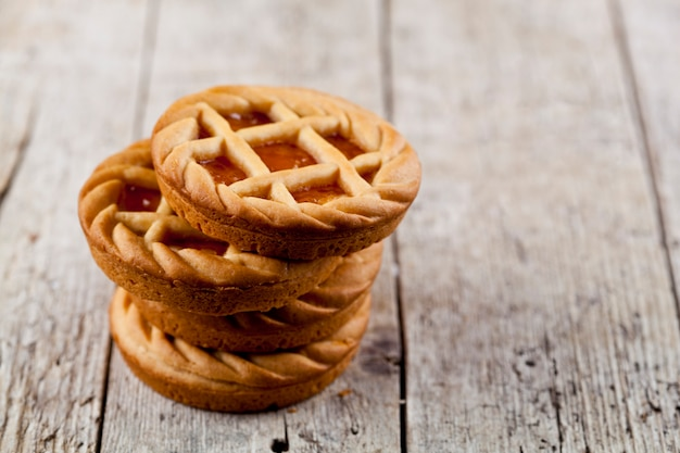 Свежие испеченные пироги с вареньем мармелада или абрикоса заполняя дальше на деревенской предпосылке деревянного стола.