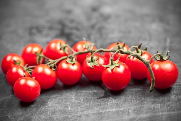 Свежий органический крупный план пука томатов вишни на черной доске.