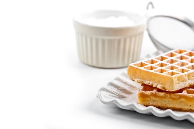 Бельгия вафли с сахарной пудрой на керамические пластины и ситечко на белом столе.