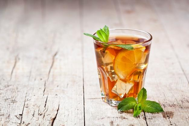 レモン、ミントの葉、素朴な木製のテーブルの上のガラスの氷と伝統的なアイスティー