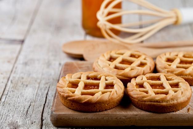 マーマレードまたはアプリコットジャムの詰め物とセラミックプレートとキッチンベーカリー用具の上に焼きたてのタルト。