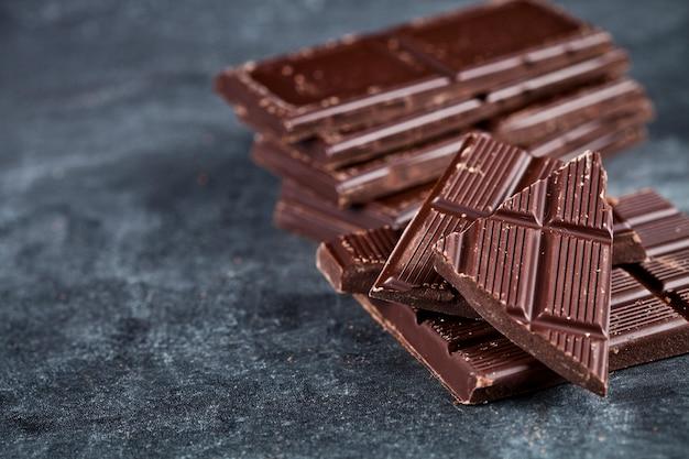 壊れたチョコレートの塊は、灰色の背景上に積層されています。