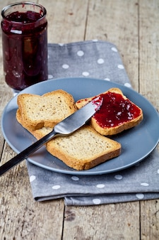 グレーのプレートと自家製チェリージャムの瓶に新鮮なトーストのシリアルパンのスライス