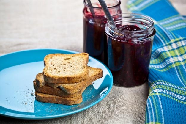 青のセラミックプレートと自家製のチェリーと野生の果実ジャムのシリアルパンのスライス