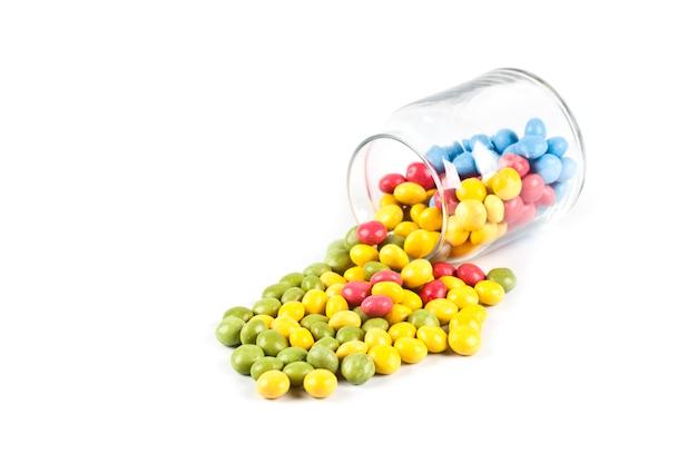 Красочные сладкие конфеты в стеклянной банке, изолированные на белом