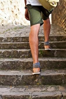 二階を歩く:茶色の革の靴の男の足のクローズアップビュー。