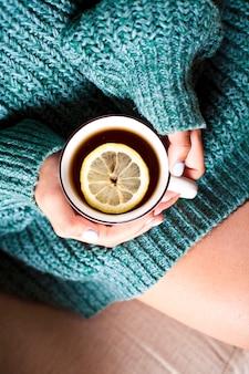 朝はレモンと熱いお茶のマグカップを保持している女性の手。