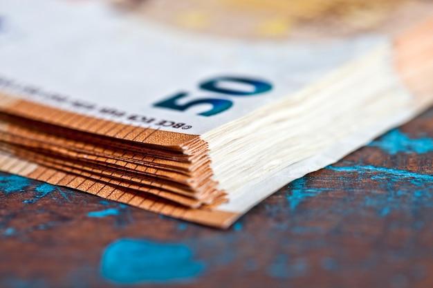 素朴な木製のテーブルのクローズアップに積み重ねられた通貨紙幣。