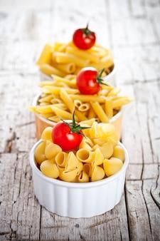 Сырые макароны и помидоры черри в трех мисках