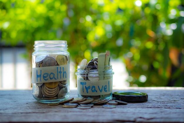 木製のテーブル、健康と旅行のコンセプト上のコインとお金の瓶