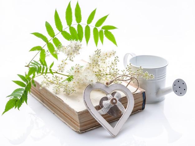 Летняя старинная композиция. старая книга, цветы рябины и украшение в форме сердца на белом