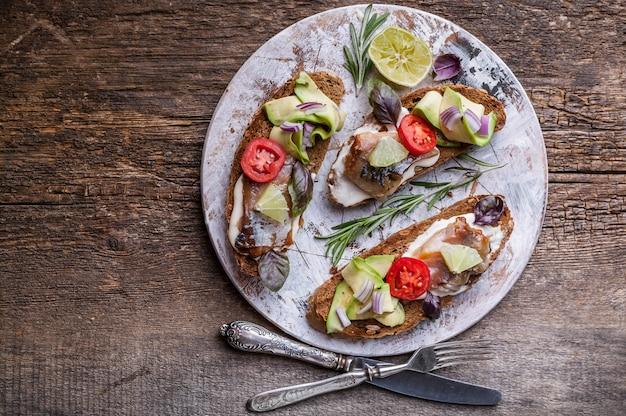 Бутерброды с копченой скумбрией, авокадо и красным луком.