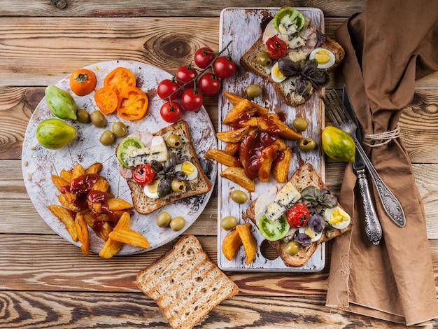Аппетитные тосты с авокадо, перепелиными яйцами, помидорами, сыром дор блю и картофелем фри.