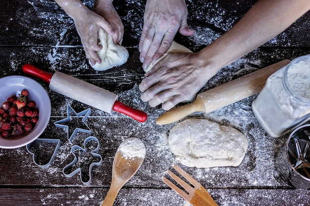 母と娘の手は、木製のテーブルに生地をこねます。ベーキング準備