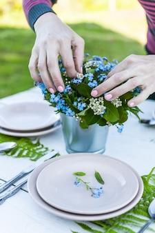 花屋は忘れな草の花とシダの葉の花束を作ります。