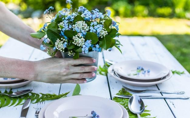 花屋は白い木製のテーブルに青いワスレナグサの花のエレガントな花束を保持します。