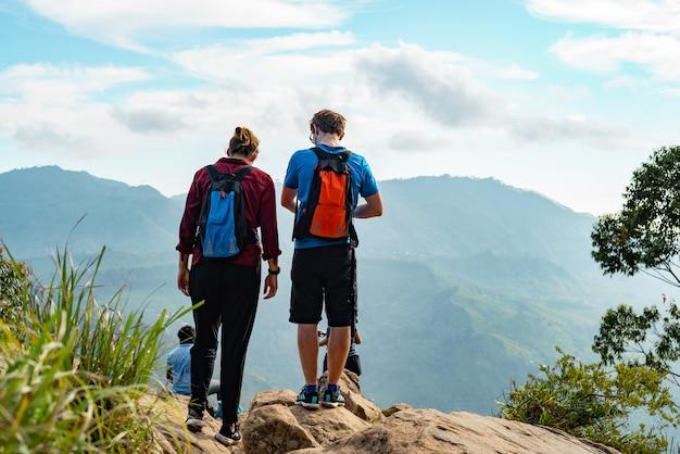 Парень и девушка снова взобрались на гору и наслаждаются видом на горы и долину в элле,